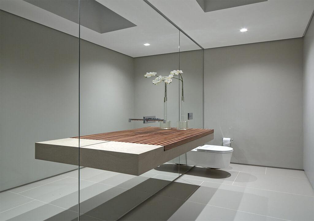 Pared forrada de espejo con lavabo encastrado